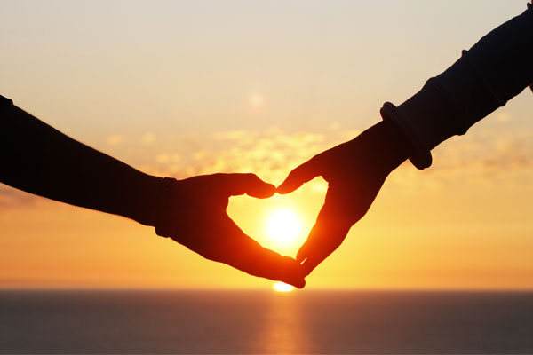 Two silhouetted hands unite to form the shape of a heart with a setting sun in the background.