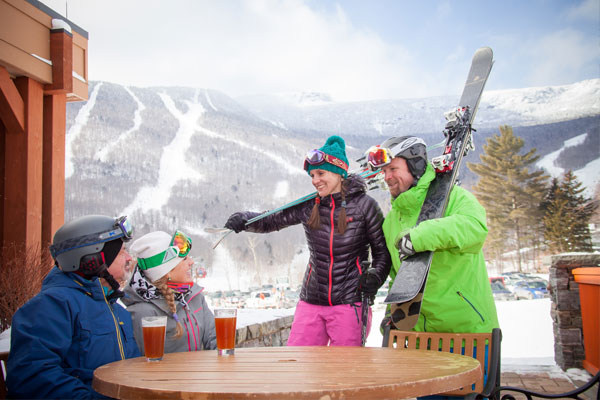 Skiers meet up for drinks at a resort pub with ski trails visible in the background.