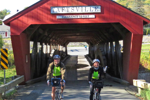 Two men riding mountain bikes across a red covered bridge.