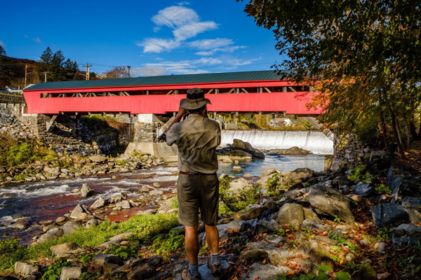 Man standing beside stream photographing a red covered bridge.