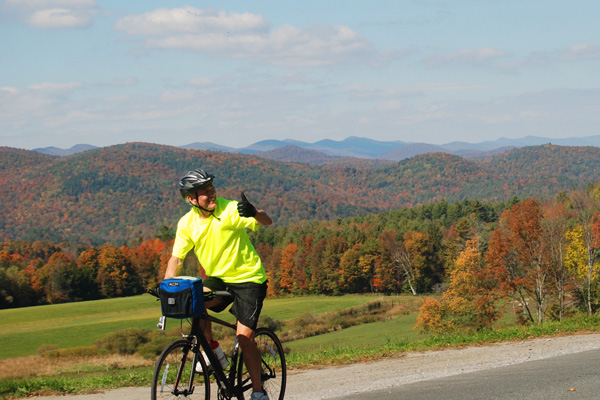 Man riding mountain bike with fall foliage in the background.