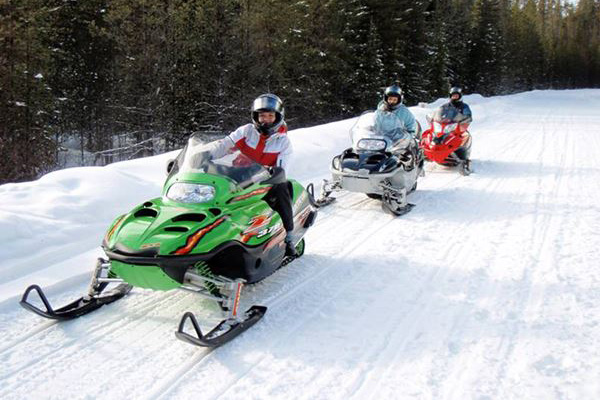 Three people riding snowmobiles on a snow covered trail.
