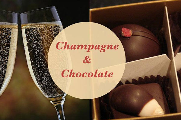 Two champagne classes clink in a toast juxtaposed next to a box of chocolate truffles.
