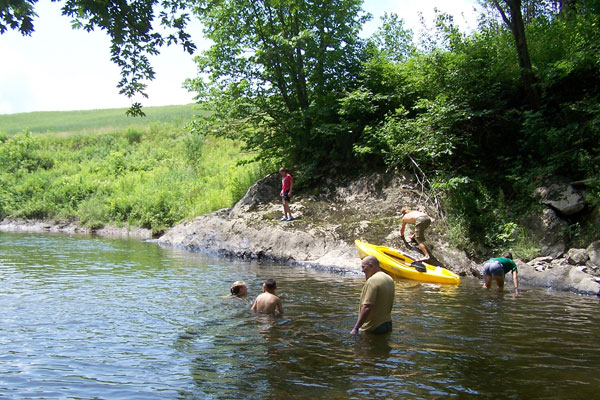 A family enjoys swimming and kayaking in the river.