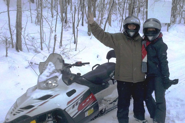 Man and woman standing by snowmobile waving .