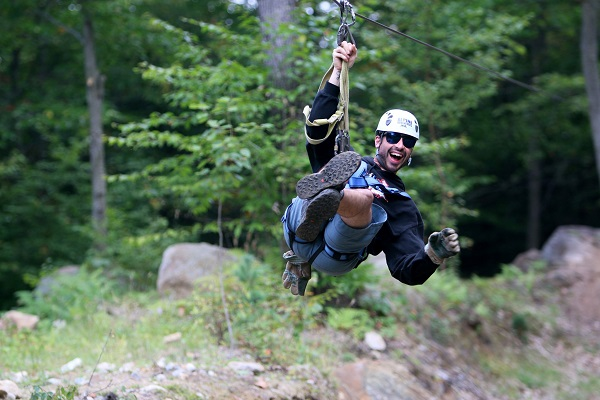 Man ziplining with big grin