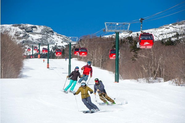 Skiiers enjoying sunny day under gondolas