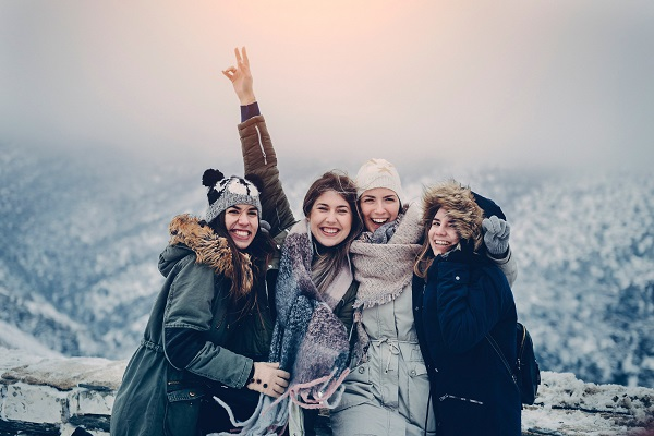 Four joyful women on top of mountain