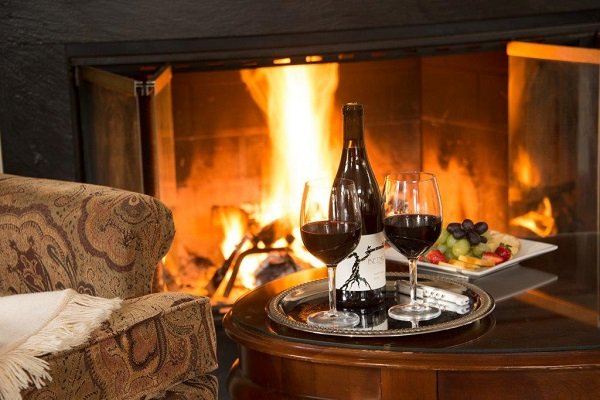 Two glasses of wine in front of blazing fireplace