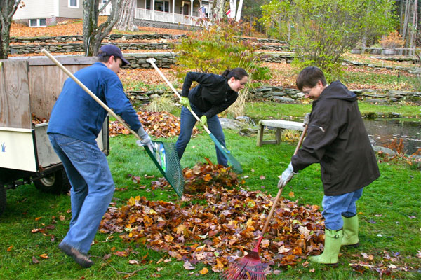Family rakes leaves together in the fall