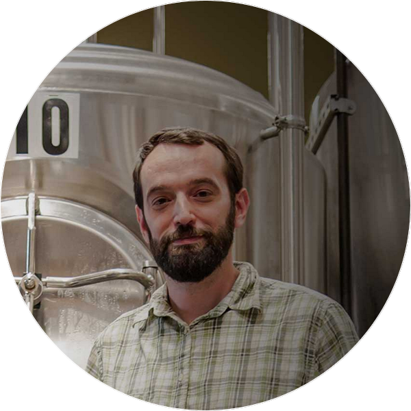 Fiddlehead brewmaster standing beside tank used to brew beer