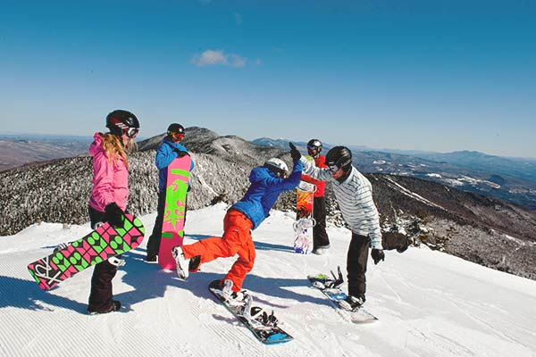 Ski and Ride Snowboarders High Five at the Mountain Top