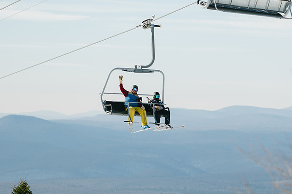 Two skiers ride the chairlift, at Bromley Mountain Resort, for their next run.
