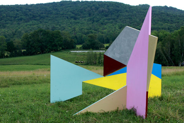 Art sculpture erected in a field with cows in the backdrop.