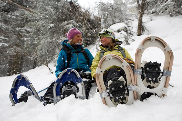 Two women stop to rest during a snowshoe hike.