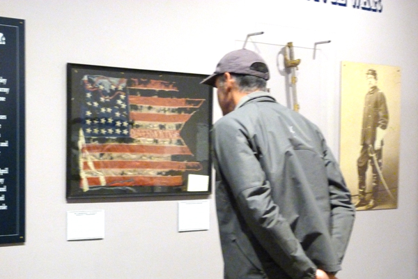 A man gazing at a framed American Flag inside a museum.