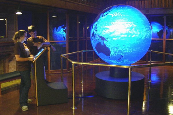 two teens look at brightly lit globe of the world