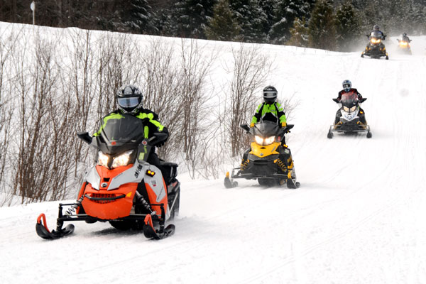 Snowmobilers riding on VAST trails.