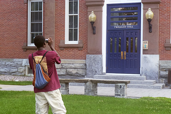 A student takes a picture of Twilight Hall at Middlebury college.